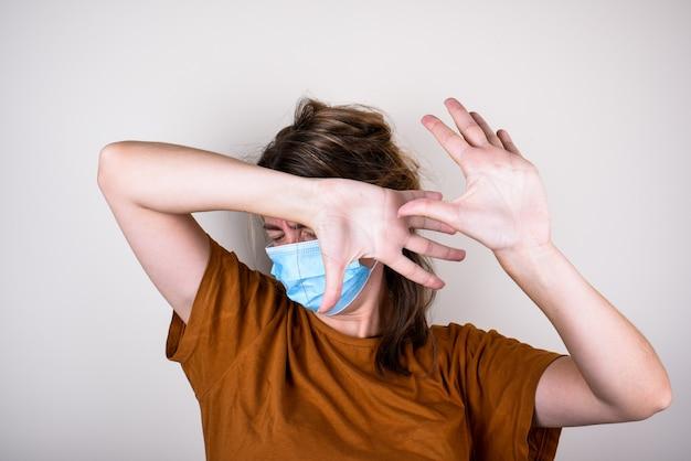 医療マスクの怖い女性は彼女の手で顔を覆い、孤立