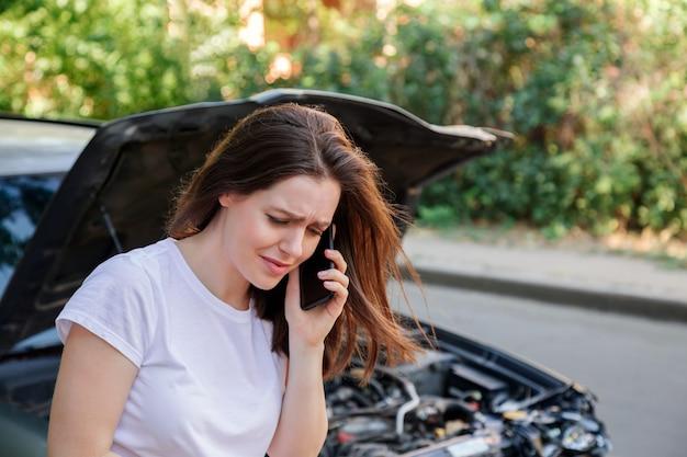 자동차 사고 후 스트레스에 무서워하는 여성이 자동차 보험에 도움을 요청했습니다. 자동차 사고로 난파 된 자동차 앞에서 우는 드라이버 여자. 위험한 도로 교통 상황.