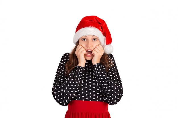 Scared woman looks nervously, biting fingernails and afraid of something, emotional girl in santa claus christmas hat isolated on white ,