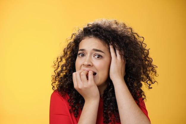 Donna spaventata che pensa troppo spaventata di essere nei guai mordendosi le dita tenendo la mano sulla testa in preda alla disperazione...