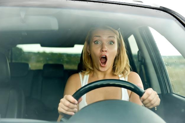 La donna spaventata grida mentre guida l'auto - all'aperto