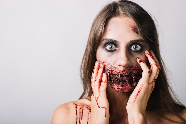 Scared woman touching damaged face with bloody hands