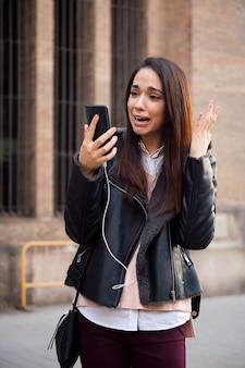 Испуганная женщина смотрит на свой телефон