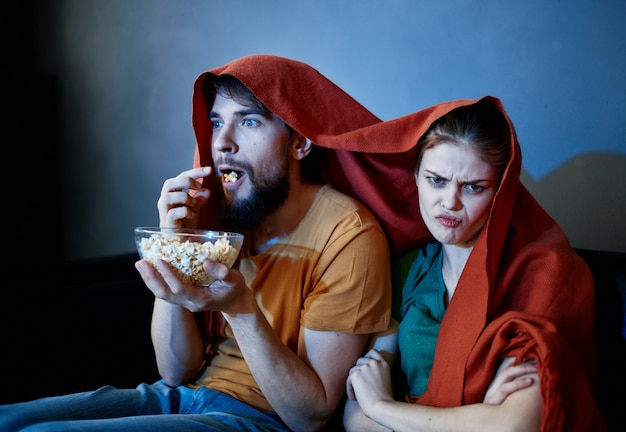 Scared woman with a red plaid on her head and a man with a plate of popcorn