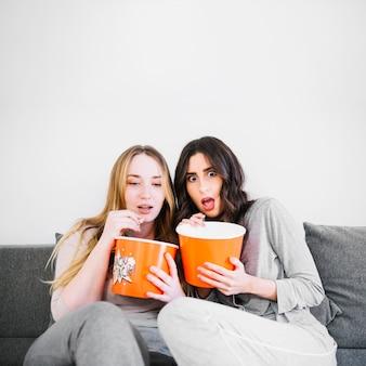 Scared women eating popcorn