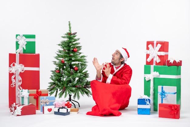 Spaventato il giovane adulto vestito da babbo natale con doni e albero di natale decorato seduto per terra su sfondo bianco