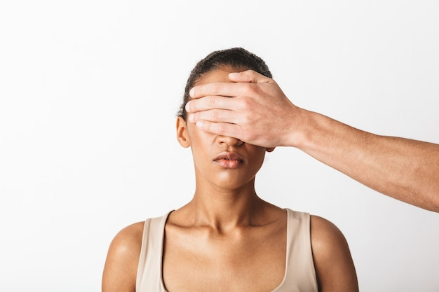 Scared young african woman sitting while man's hand coning her eyes isolated on white