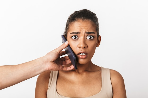 남자의 손이 흰색에 고립 된 그녀의 귀에 휴대 전화를 들고 앉아 무서 워 젊은 아프리카 여자