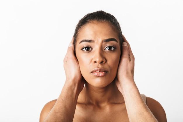 男の手が白で隔離された彼女の耳を円錐形にしながら座っている怖い若いアフリカの女性