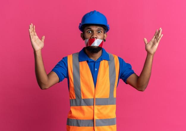 Giovane uomo costruttore afroamericano spaventato in uniforme con la bocca del casco di sicurezza sigillata con nastro di avvertimento in piedi con le mani alzate isolate su sfondo rosa con spazio di copia