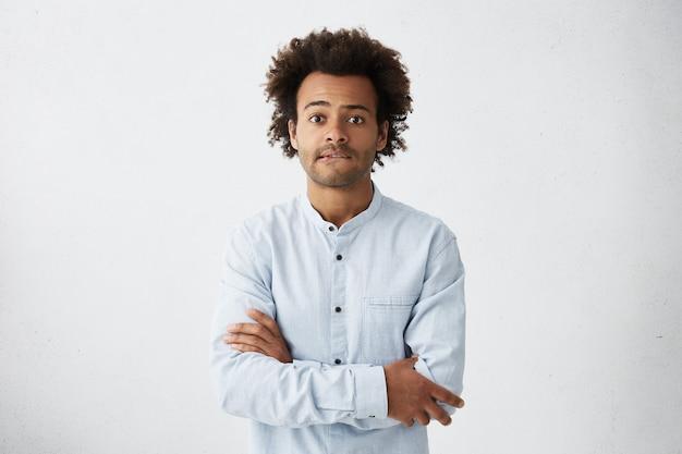 カジュアルなシャツを着た若いアフロアメリカンの男性が腕を組んで唇を噛んで怖がって