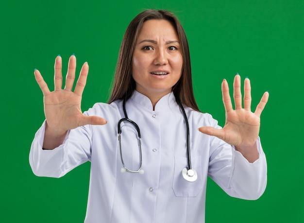 緑の壁に隔離された拒否ジェスチャーをしている正面を見て医療ローブと聴診器を身に着けている怖い若いアジアの女性医師