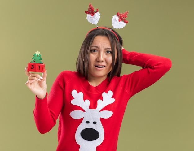 オリーブグリーンの壁で隔離の頭に手を置くクリスマスのおもちゃを保持しているクリスマスの髪のフープを身に着けている怖い若いアジアの女の子