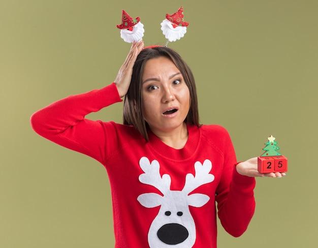 Giovane ragazza asiatica spaventata che porta il cerchio dei capelli di natale che tiene il giocattolo di natale che mette la mano dietro la testa isolata sulla parete verde oliva