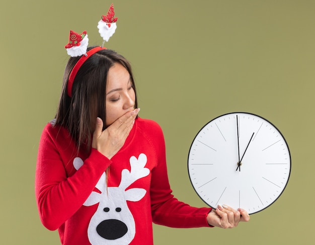 Scared young asian girl wearing christmas hair hoop holding and looking at wall clock covered mouth with hand isolated on olive green background