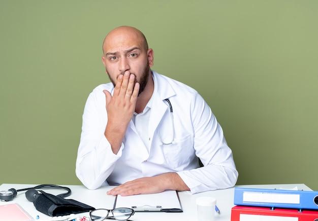 Spaventato giovane medico maschio calvo che indossa abito medico e stetoscopio seduto al lavoro di scrivania