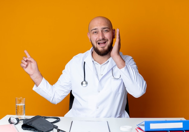 Scared young bald male doctor wearing medical robe and stethoscope sitting at work desk
