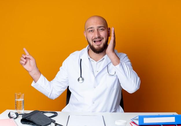 Spaventato giovane medico maschio calvo che indossa veste medica e stetoscopio seduto alla scrivania