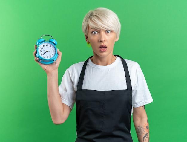 緑の背景に分離された目覚まし時計を保持している制服を着た若い美しい女性の理髪師を怖がらせる