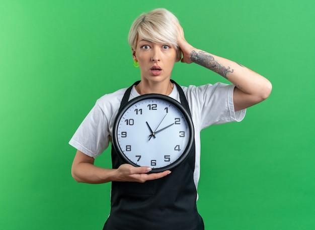 Spaventata giovane bella barbiere femminile in uniforme che tiene la serratura a muro e mette la mano sulla testa isolata su sfondo verde