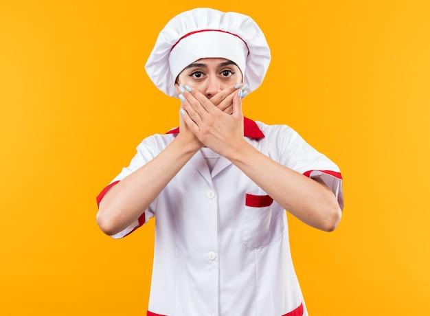 La giovane bella ragazza spaventata in uniforme da chef ha coperto la bocca di hnads