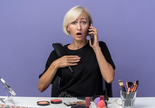 겁에 질린 아름다운 소녀는 화장 도구를 들고 탁자에 앉아 파란 배경에 격리된 빗을 들고 전화로 말한다