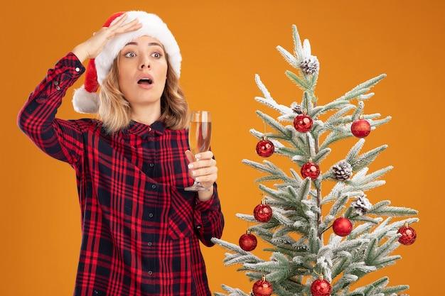 오렌지 배경에 고립 손으로 거리를 찾고 샴페인 잔을 들고 크리스마스 모자를 쓰고 크리스마스 트리 근처에 서 무서 워 젊은 아름 다운 소녀