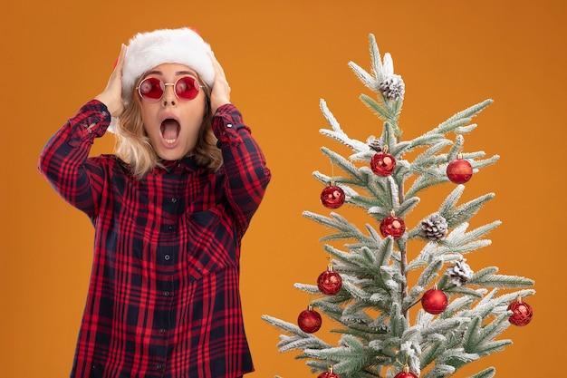 オレンジ色の背景で隔離のガラスのつかんだ頭とクリスマス帽子をかぶってクリスマスツリーの近くに立っている怖い若い美しい少女