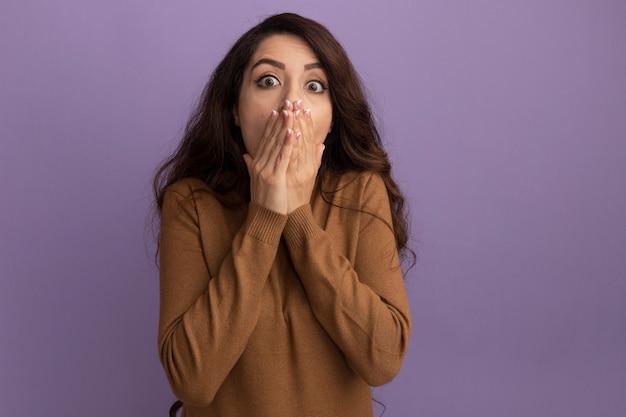 보라색 벽에 고립 된 손으로 갈색 터틀넥 스웨터 덮여 얼굴을 입고 무서 워 젊은 아름 다운 소녀