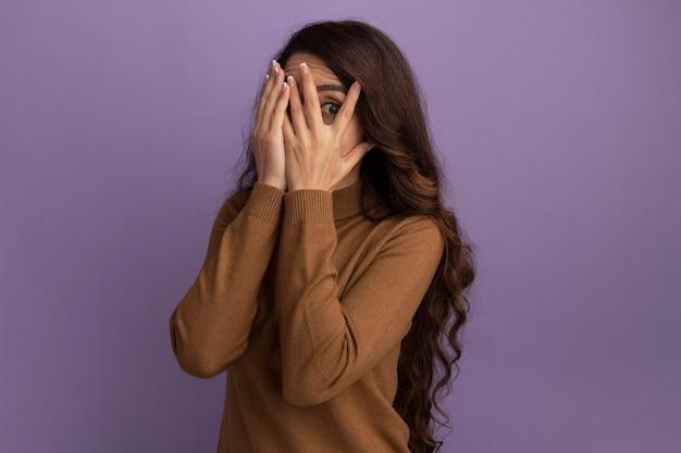 Spaventata giovane bella ragazza che indossa maglione dolcevita marrone viso coperto con le mani isolate sulla parete viola