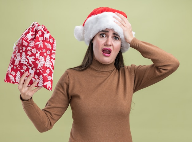 Giovane bella ragazza spaventata che porta il cappello di natale che tiene la borsa di natale che mette la mano sulla testa isolata su fondo verde oliva Foto Gratuite