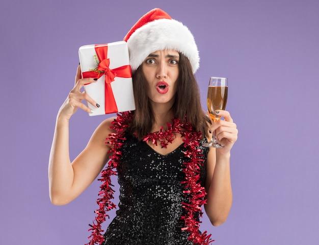 Giovane bella ragazza spaventata che porta il cappello di natale con la ghirlanda sul collo che tiene il contenitore di regalo con un bicchiere di champagne isolato su sfondo viola