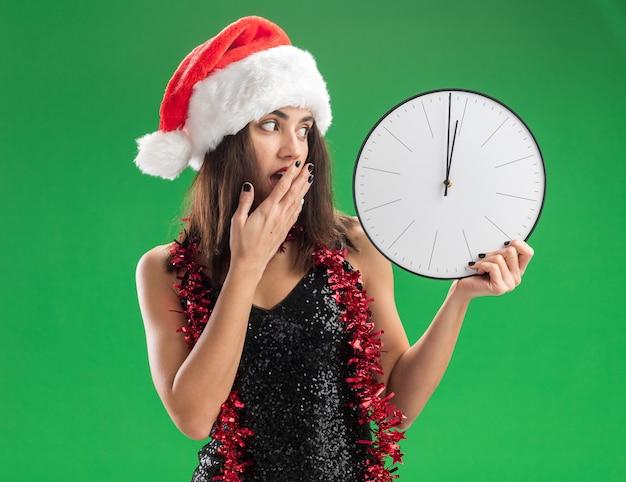 Giovane bella ragazza spaventata che porta il cappello di natale con la ghirlanda sul collo che tiene e guardando l'orologio da parete ha coperto la bocca con la mano isolata sulla parete verde