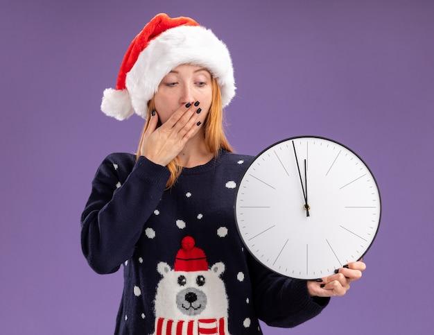 크리스마스 스웨터와 모자를 들고 벽 시계를보고 무서워 젊은 아름 다운 소녀 보라색 배경에 고립 된 손으로 입을 덮여