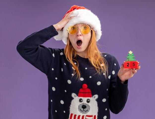 Испуганная молодая красивая девушка в рождественском свитере и шляпе с очками, держащая рождественскую игрушку, положив руку на голову, изолированную на фиолетовом фоне