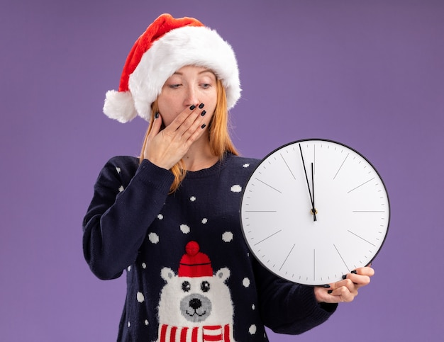 Scared young beautiful girl wearing christmas sweater and hat holding and looking at wall clock covered mouth with hand isolated on purple background