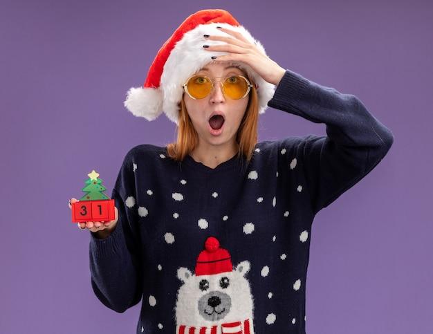 Giovane bella ragazza spaventata che indossa il maglione e cappello di natale con gli occhiali che tengono il giocattolo di natale che mette la mano sulla fronte isolata su fondo viola Foto Gratuite