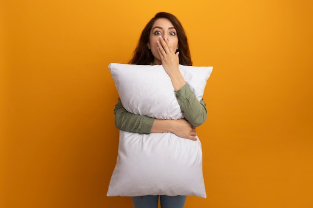 Испуганная молодая красивая девушка в оливково-зеленой футболке обняла подушку, прикрыла рот рукой, изолированной на желтой стене с копией пространства