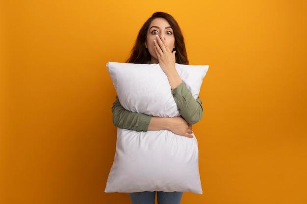 La giovane bella ragazza spaventata che porta la maglietta verde oliva ha abbracciato la bocca coperta del cuscino con la mano isolata sulla parete gialla con lo spazio della copia