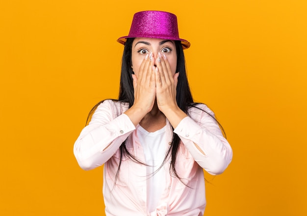Scared young beautiful girl wearing party hat covered face with hands