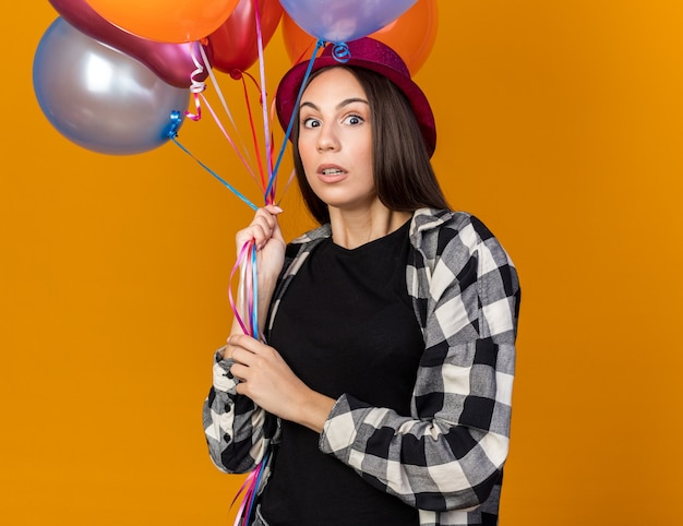 Scared young beautiful girl wearing party hat holding balloons isolated on orange wall