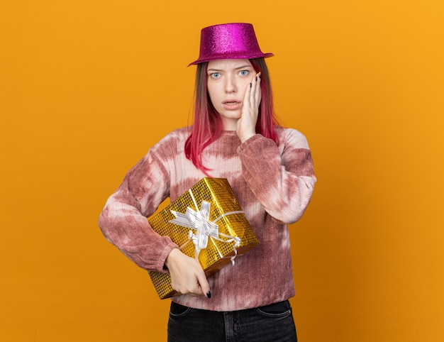 Scared young beautiful girl wearing party hat holding gift box putting hand on cheek