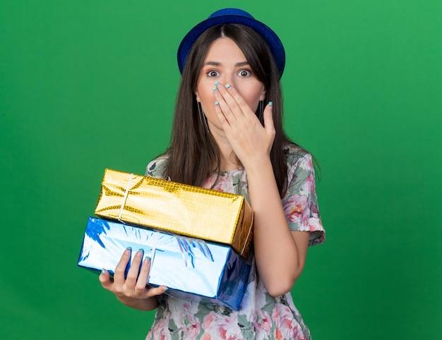 手で口を覆ったギフトボックスを保持しているパーティーハットを身に着けている怖い若い美しい少女