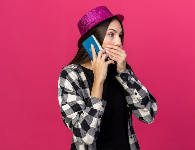 Scared young beautiful girl wearing party hat speaks on phone covered mouth with hand