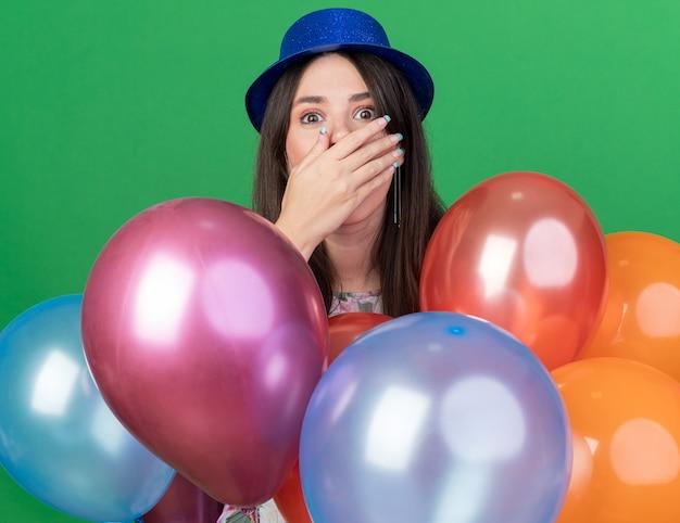 風船の後ろに立っているパーティーハットを身に着けている怖い若い美しい少女は手で口を覆った