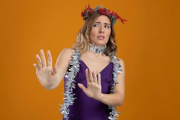 茶色の背景で隔離の側に手を差し伸べる花輪と紫色のドレスを着て怖い若い美しい少女