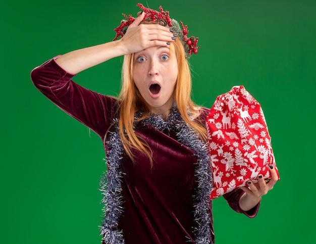 緑の壁に分離された額に手を置いてクリスマス バッグを保持している首に花輪と花輪の赤いドレスを着て怖がっている美しい少女