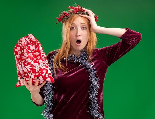 녹색 배경에 고립 된 머리에 손을 넣어 크리스마스 가방을 들고 목에 화 환과 갈 랜드와 빨간 드레스를 입고 무서 워 젊은 아름 다운 소녀