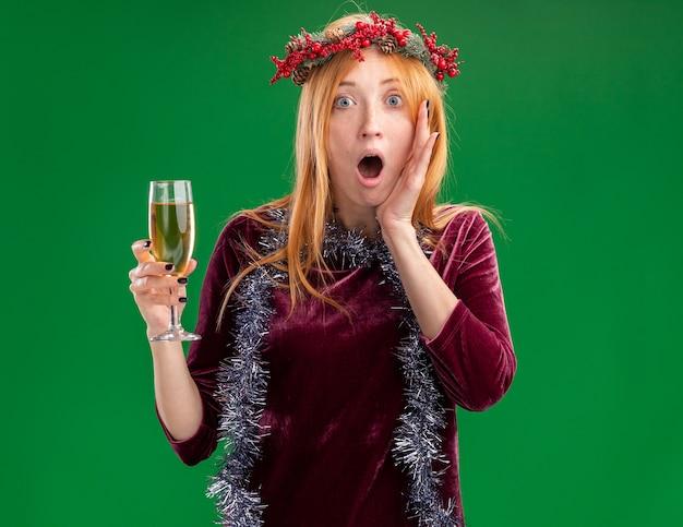 緑の背景で隔離の頬に手を置くシャンパンのガラスを保持している首に花輪と花輪と赤いドレスを着て怖い若い美しい少女