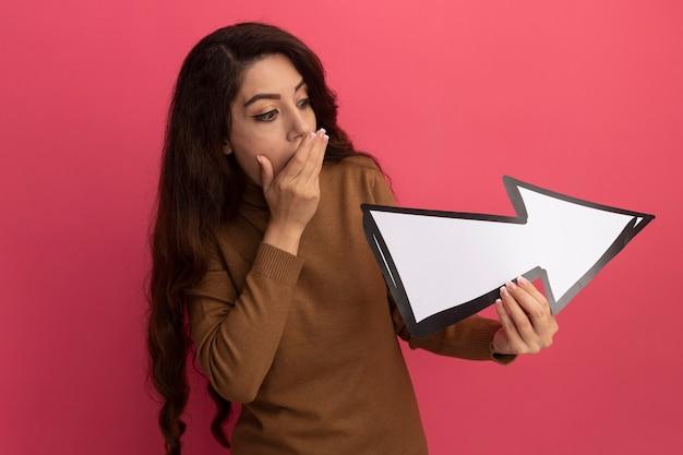 Giovane bella ragazza spaventata che indossa maglione a collo alto che tiene e guardando il segno di direzione isolato sul muro rosa